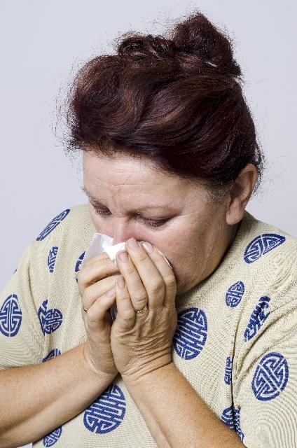 鼻をティッシュで押さえる女性